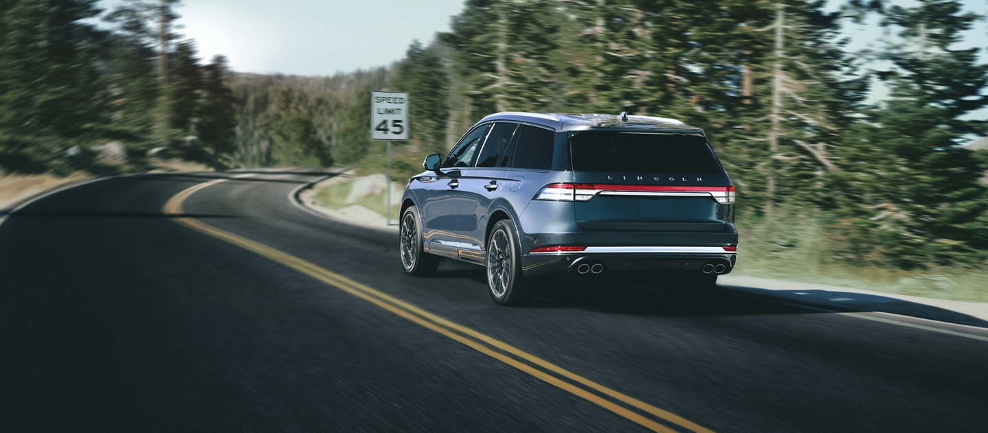 A Lincoln Aviator is shown being driven on a winding road as it approaches a speed limit sign