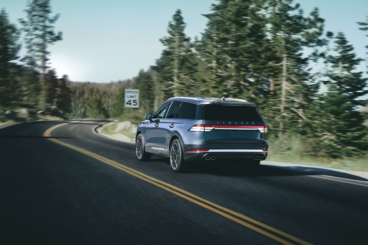 A Lincoln Aviator is shown being driven on a mountain road as it approaches a speed limit sign