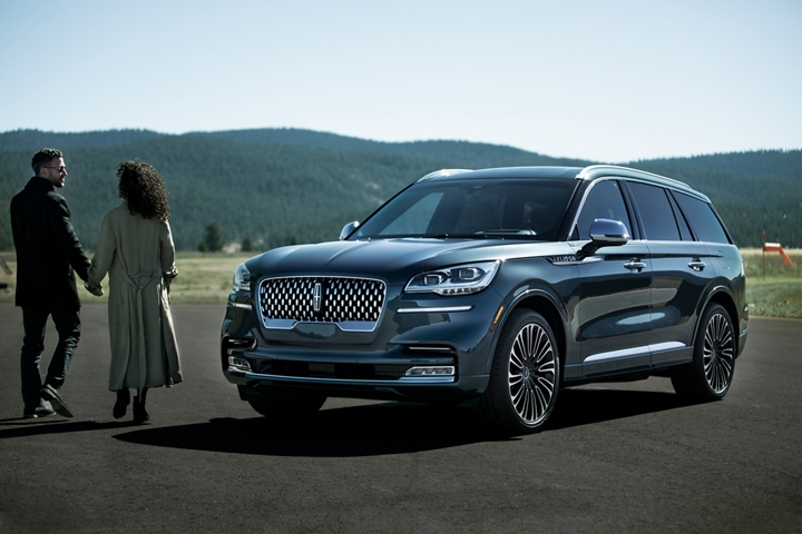 A couple is shown approaching a Parked Lincoln Aviator Black Label in the Flight themes stunning Blue Diamond exterior color
