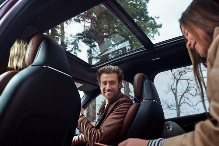 A family is shown in a parked Lincoln Aviator with the panoramic vista roof above them allowing golden light into the cabin