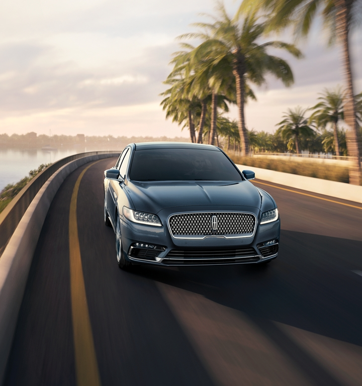 An impressive look at the front grille of a fast-moving Lincoln Continental on a coastal highway