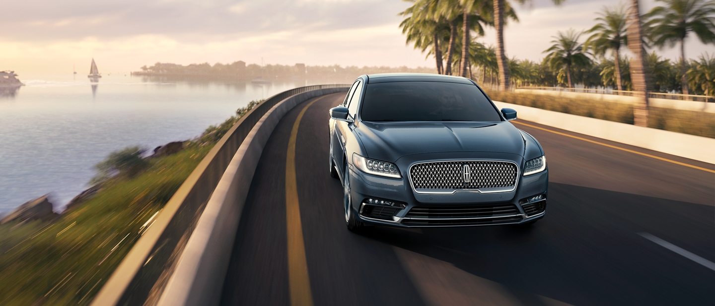 A fast-moving Lincoln Continental demonstrates its agility while cornering on a coastal highway