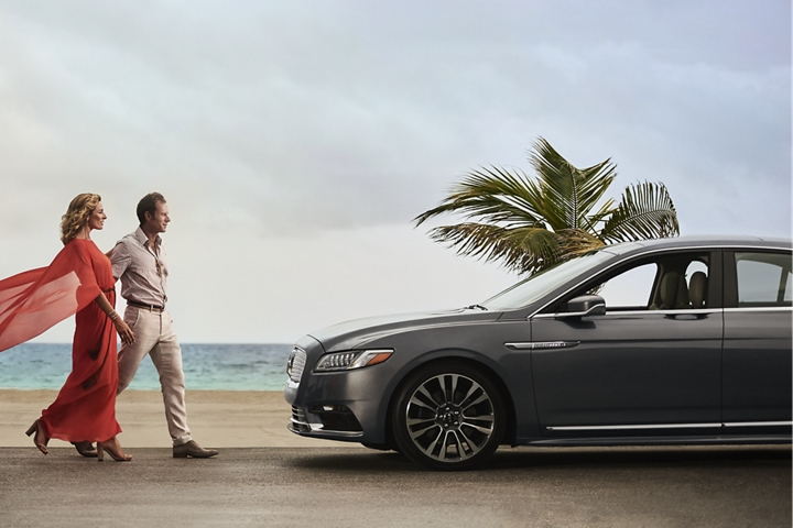 A couple approaches a Lincoln Continental parked by an inviting sandy beach