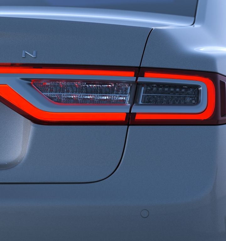 A man approaches a Continental as the LED taillamps illuminate as part of the Lincoln Embrace