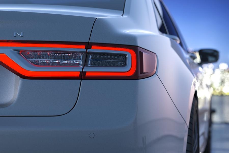 Un hombre se acerca a un Continental iluminado por las luces LED traseras como parte del Lincoln Embrace
