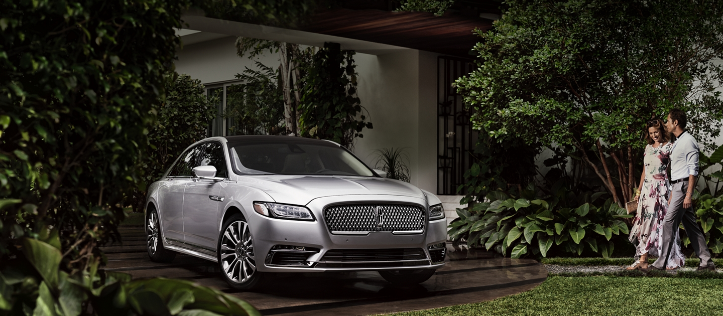 A couple approaches a Lincoln Continental parked in a driveway surrounded by lush greenery