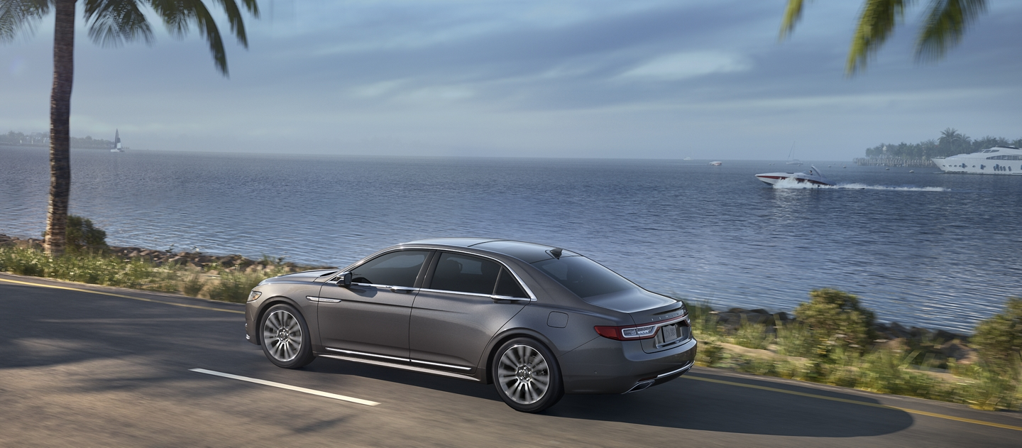 The Lincoln Continental seen in the Magnetic Gray exterior color is being driven along a coastline