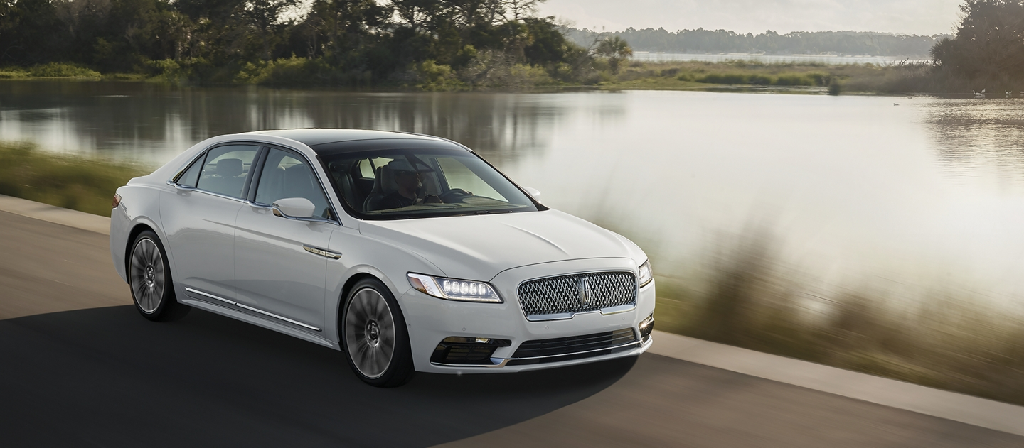 A Lincoln Continental with is shown being driven swiftly to demonstrate the adaptive suspension