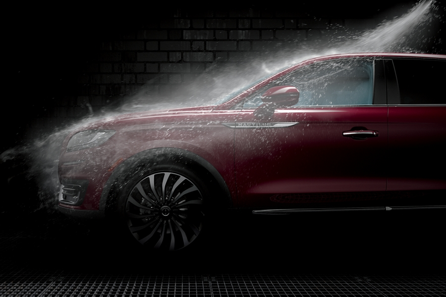 A fine spray of water mist showers a Lincoln in a car wash
