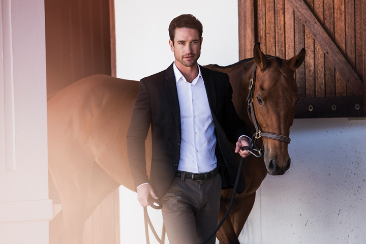 A nicely dressed man is shown guiding a horse through a stable to represent the inspiration of the Thoroughbred theme