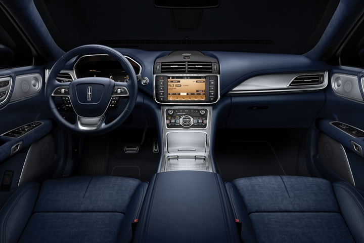 An image of the interior of a Lincoln Continental shows the view from the rear seat looking forward
