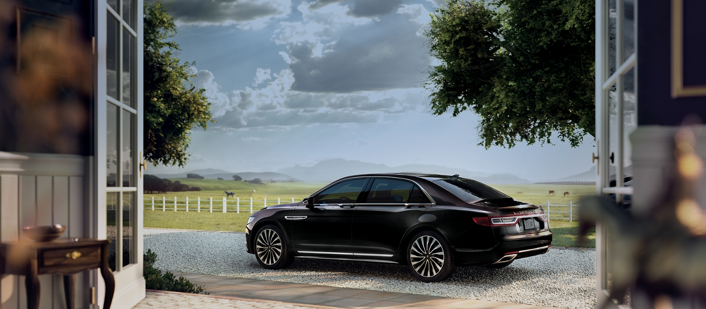 A Lincoln Black Label Continental in the thoroughbred theme is shown on the driveway of a sprawling horse ranch