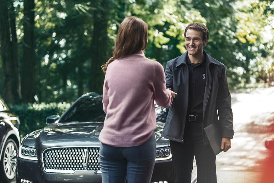 A Lincoln representative is shown handing over a set of keys to a customer after Pickup and delivery service
