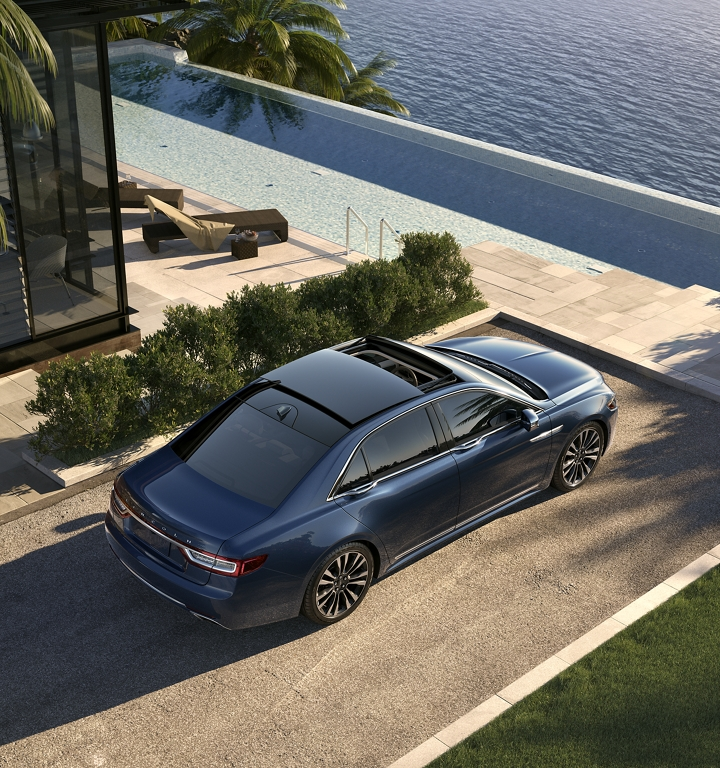 The Continental is shown parked at an inviting waterfront home while it shows off its available retractable moonroof