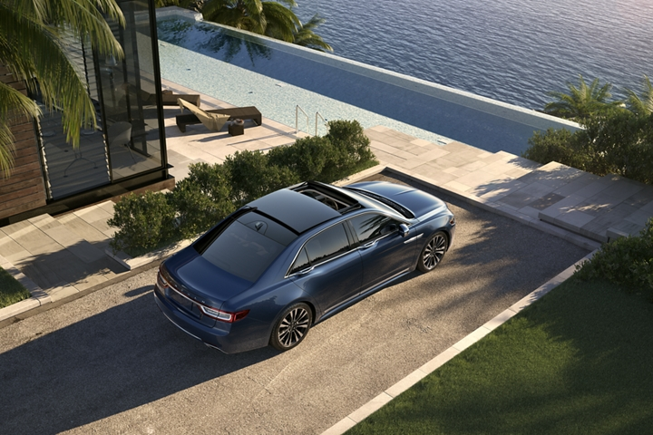 A Lincoln Continental in the Blue Diamond Metallic exterior color is parked in the driveway of an elegant shoreline home
