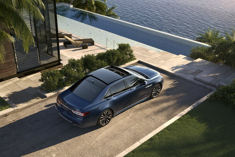 The Lincoln Continental in Rhapsody Blue is shown parked beside a shoreline home