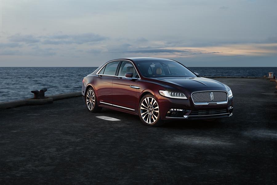 El Lincoln Continental en borgoña aterciopelado con tinte transparente metalizado proyecta el tapete de bienvenida iluminado con el logo Lincoln en el piso