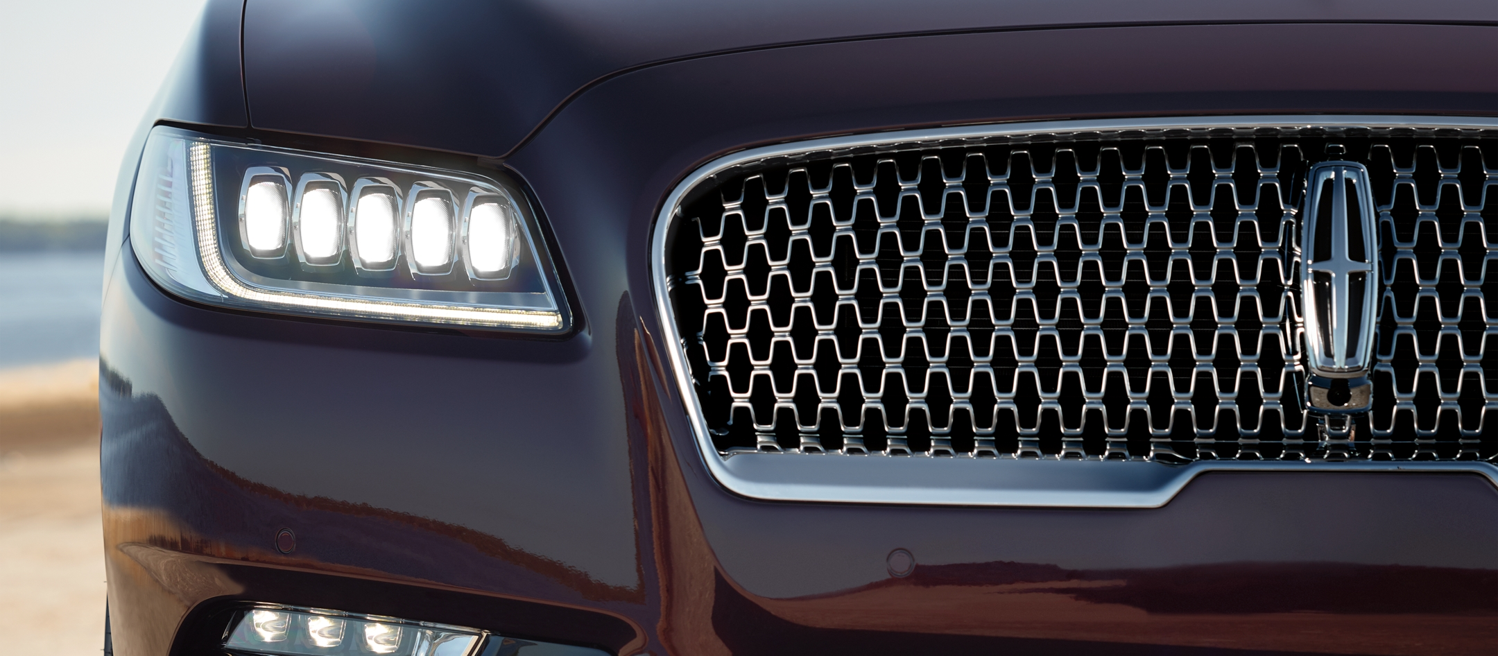 A close up image shows the illuminated headlamps of a Lincoln Continental