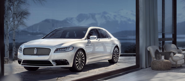 Se muestra un Lincoln Black Label Continental con el tema Chalet estacionado en la entrada de una lujosa casa de montaña