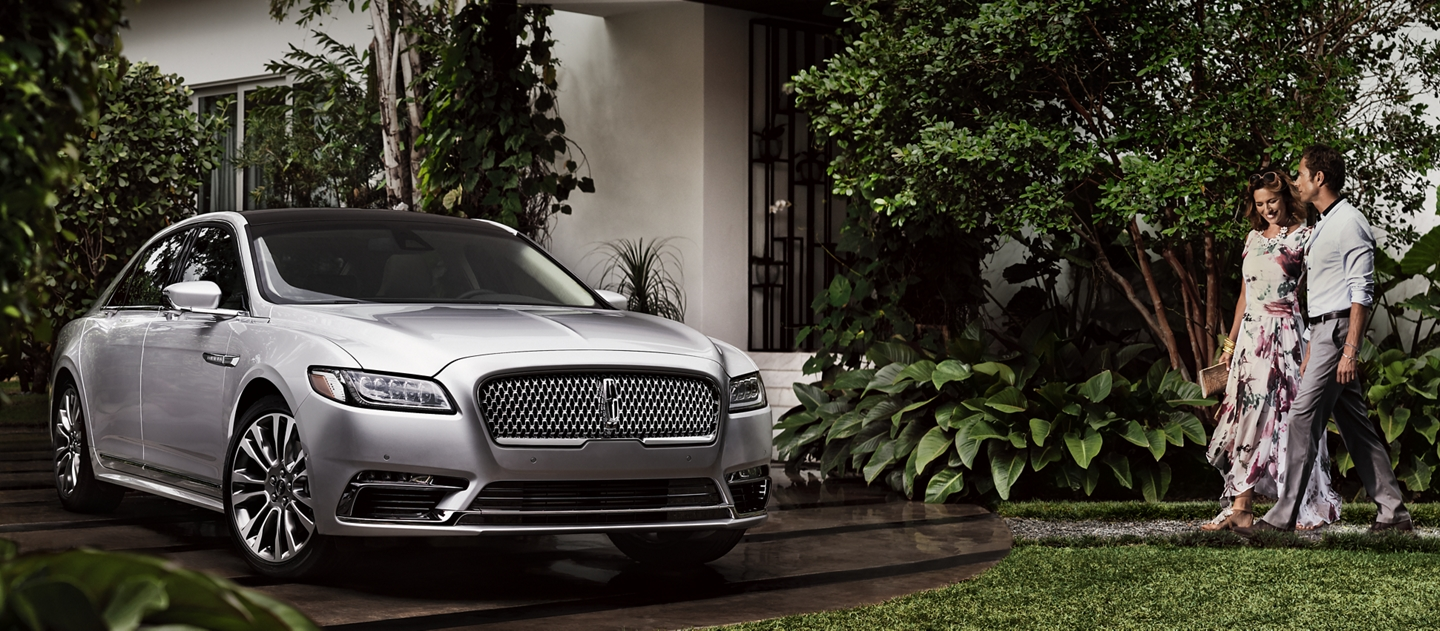 A couple is shown approaching a 2020 Lincoln Continental parked in a driveway surrounded by lush greenery