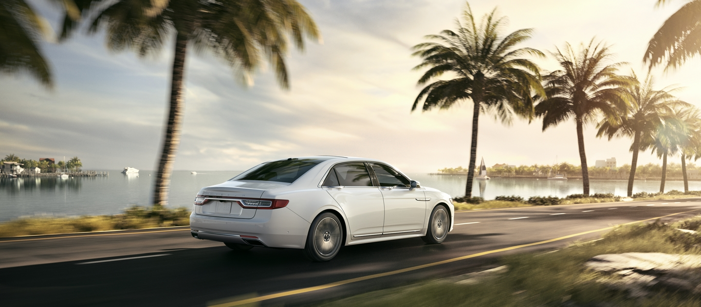 A 2020 Lincoln Continental is shown being taken out for a spirited drive along a palm tree lined coastal highway