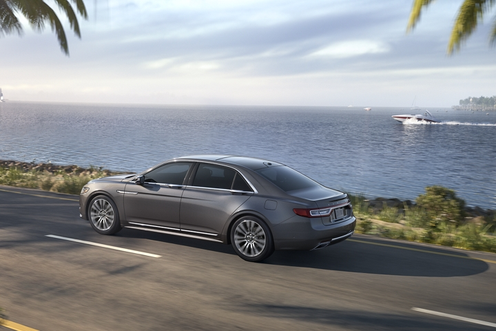 The 2020 Lincoln Continental shown in the Magnetic Gray exterior color is being driven along a coastline
