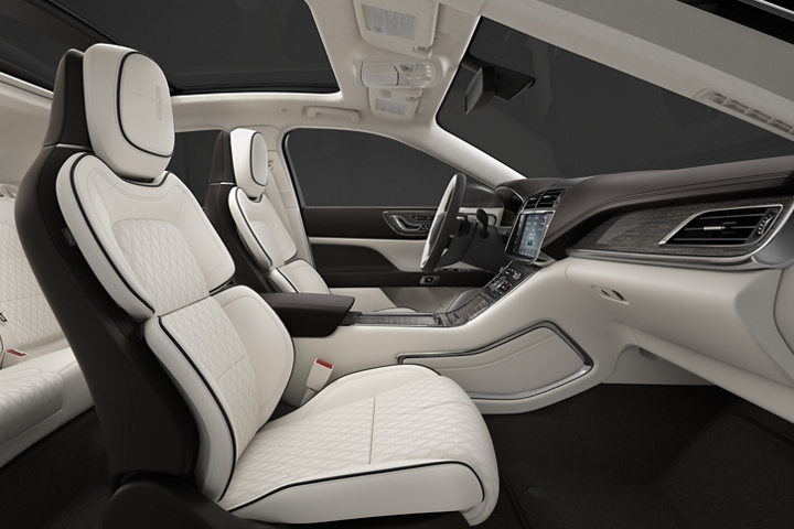 A side view shows the front passenger and drivers seats in the rich white of the Chalet theme and soothing silverwood inlays
