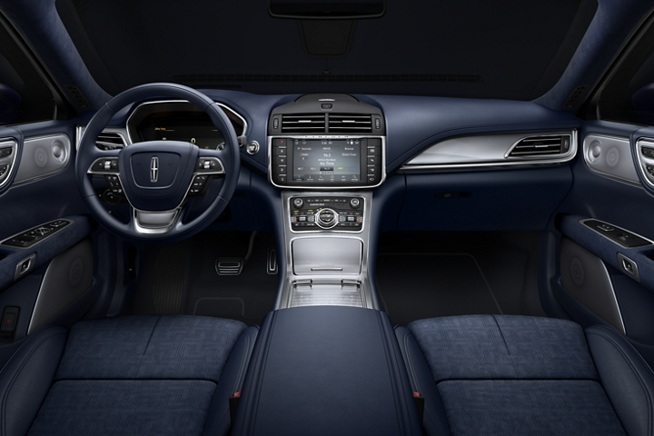 The interior of a Lincoln Continental is shown from the rear seat looking forward with aluminum inlay offering stylish contrast