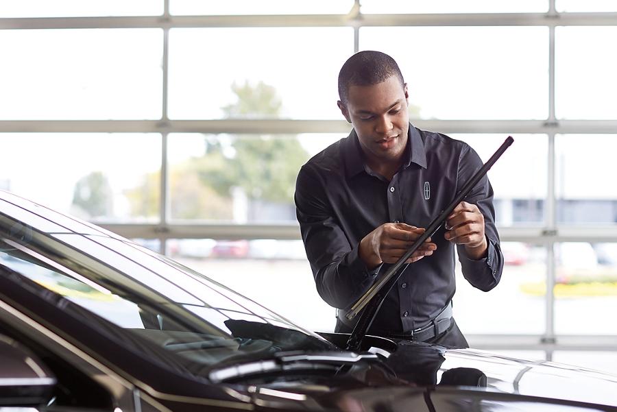Se muestra un técnico de servicio de Lincoln ajustando las escobillas del limpiaparabrisas de un vehículo Lincoln en el área de servicio de un concesionario