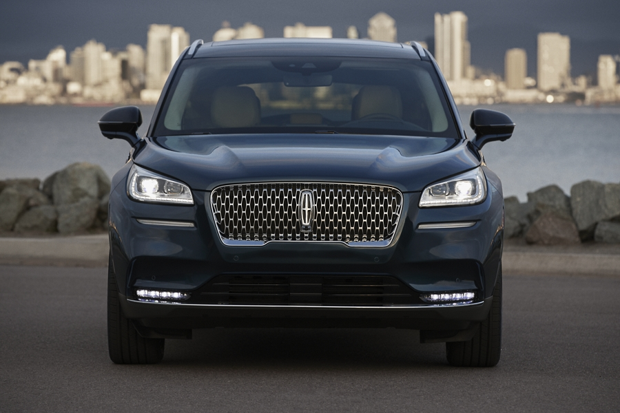 The front end of a 2020 Lincoln Corsair in flight blue is illuminated with bright headlamps that cut through the dusk