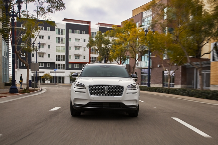 A Lincoln Corsair in pristine white is being driven through an urban setting with responsive performance