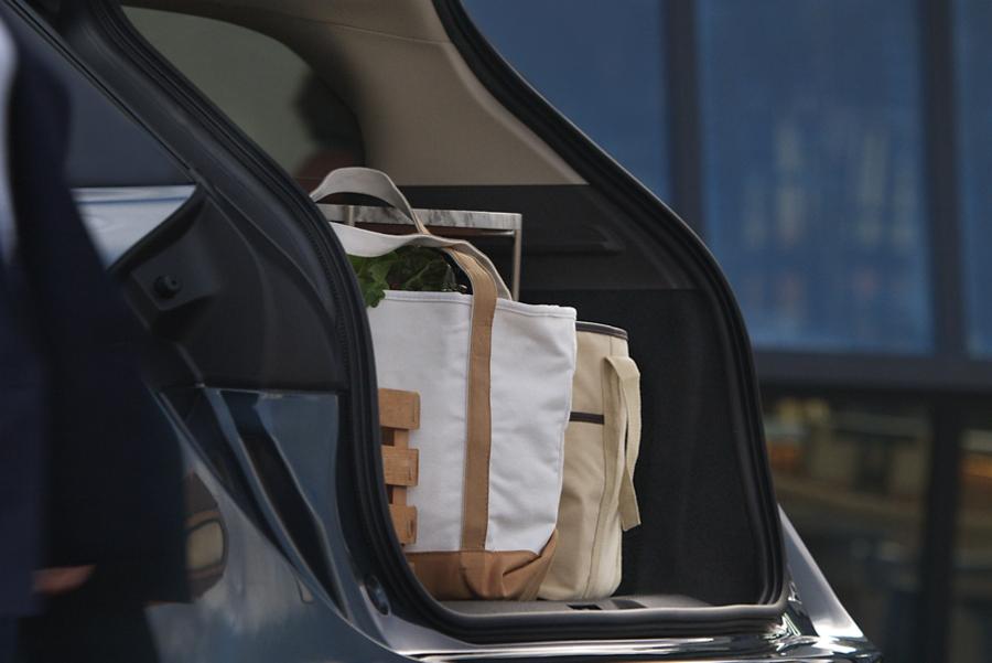 La cajuela abierta de una Lincoln Corsair en Azul Flight con bolsas de lona repletas de productos de marcado para mostrar la capacidad de carga.