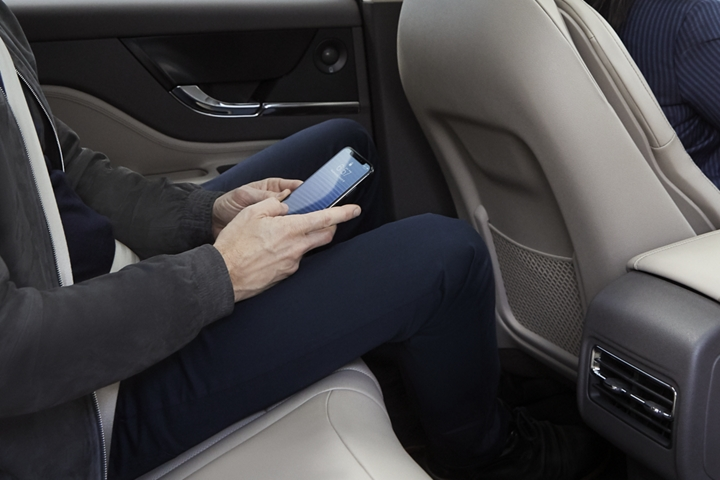 A backseat passenger in a sandstone interior enjoys the convenient 4 G L T E wi fi hotspot on his smartphone device