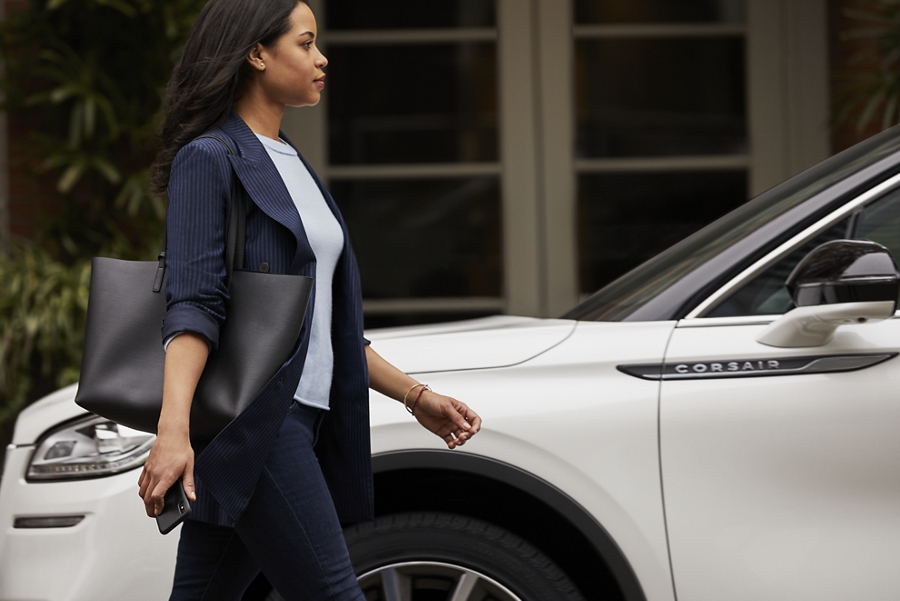 Una mujer se aproxima hacia el lado del conductor de una Lincoln Corsair en Blanco Inmaculado sin levantar un dedo