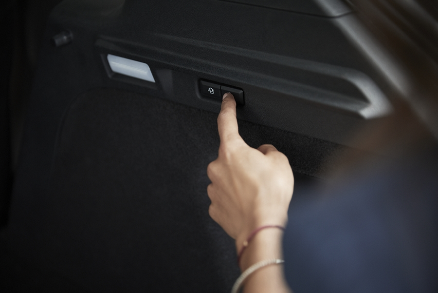 Una mujer oprime el botón eléctrico de la característica Easy Fold de la cajuela para plegar los asientos sin esfuerzo y brindar espacio de carga