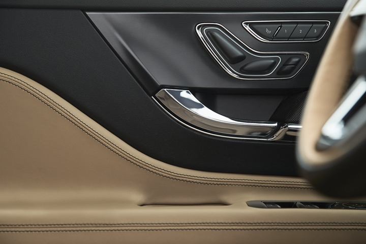 The door controls of an ebony and cashew interior show off different settings that can be set with personal profiles