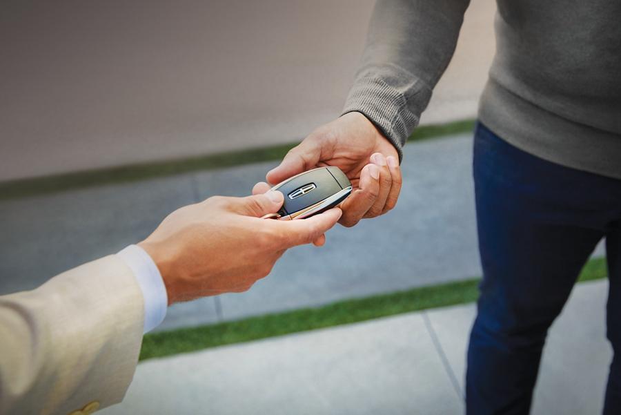 Un conductor y representante de Lincoln están intercambiando llaves Lincoln por un práctico servicio de recogida y entrega Lincoln