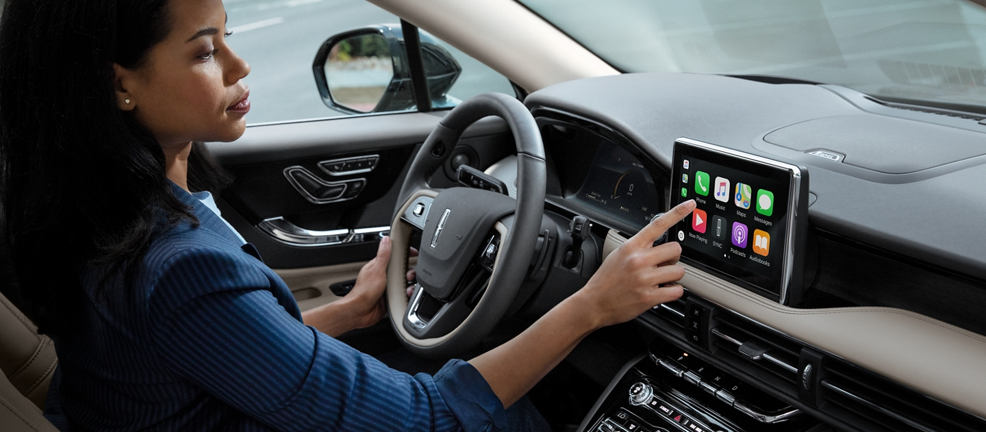 A woman in the drivers seat of a 2020 Lincoln Corsair is touching the center digital screen to connect to Apple Carplay