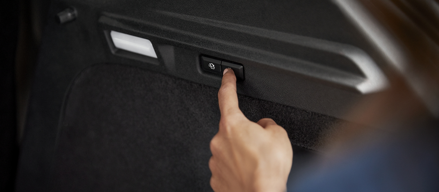 A woman pushes the easy fold power button in the cargo area to effortlessly fold seats and open up cargo space