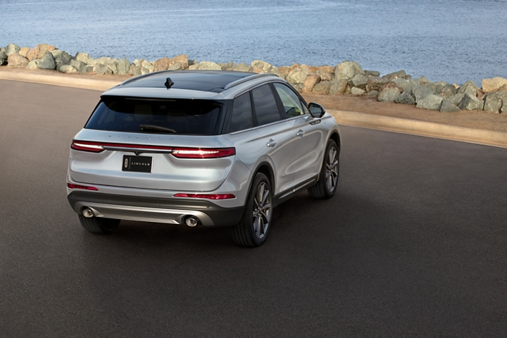 A 2020 Lincoln Corsair is parked overlooking the water as daylight illuminates the back end floating chrome horizontal lights and design lines