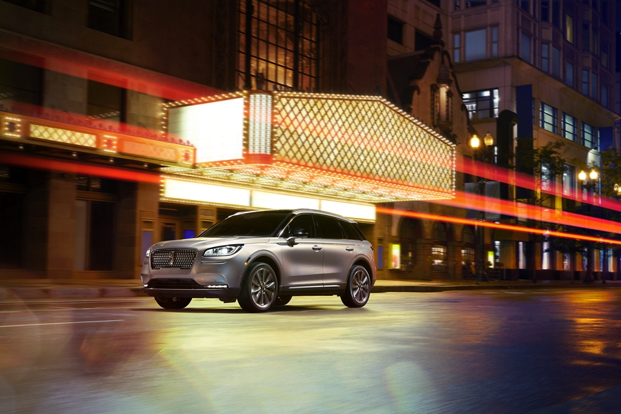 A 2020 Lincoln Corsair in ingot silver is being driven by a theater as ambient lights are reflected in the streets and the shape of the body