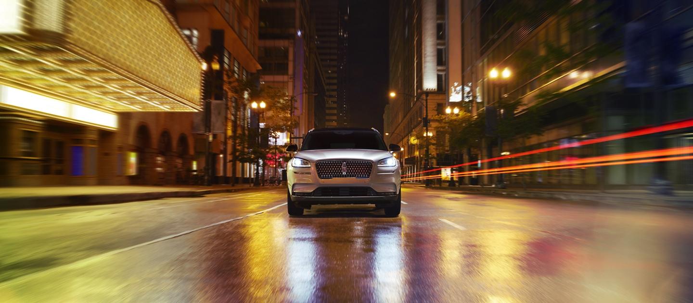 Una imagen de frente de una Lincoln Corsair 2020 andando por una calle de ciudad de noche