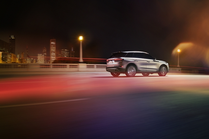 A 2020 Lincoln Corsair is being driven through an urban setting at night with responsive performance