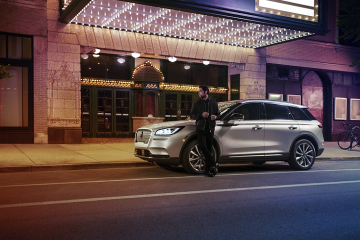 A 2020 Lincoln Corsair is parked outside a theatre as the driver relaxes against the frame and lights illuminate the floating roofline and body