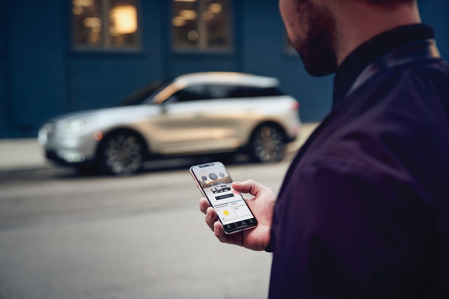 Un hombre sostiene su teléfono mientras mira la aplicación Lincoln Way, podemos ver su Lincoln Corsair 2020 al fondo contra una pared de ladrillo azul