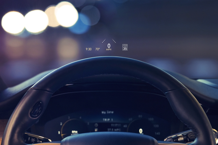 The head up display projects data on the windshield above the steering wheel inside a 2020 Lincoln Corsair as the driver navigates the city at night