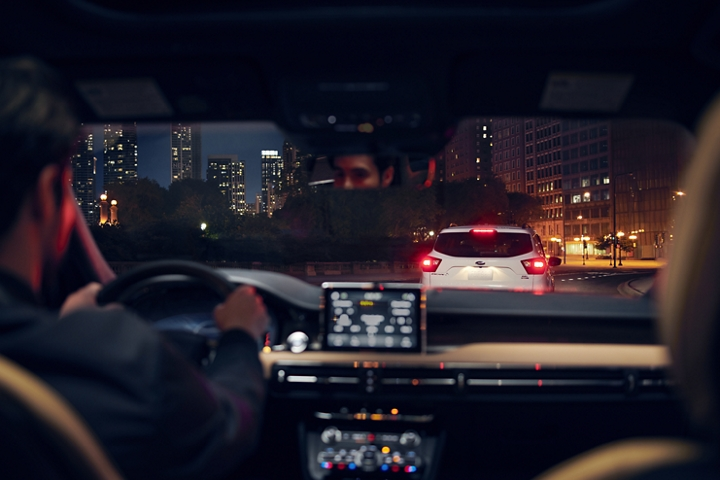 Through the windshield of a 2020 Lincoln Corsair we see a vehicle with its brake lights illuminated ahead on a street with a skyline in the distance