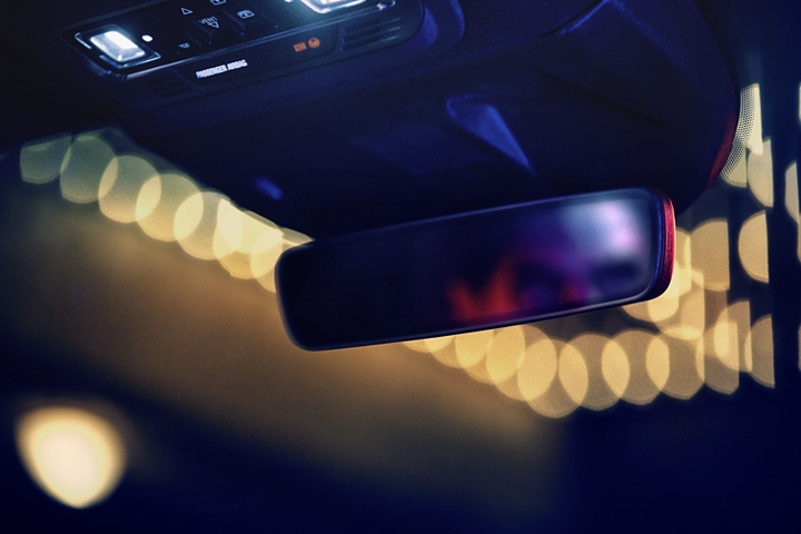 A blurred face is shown in the reflection of the sleek frameless rearview mirror as soft warm theatre marquee lights glow through the windshield