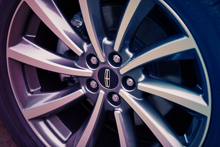 A detail shot of a wheel shows off radial design lines and elegant chrome accents