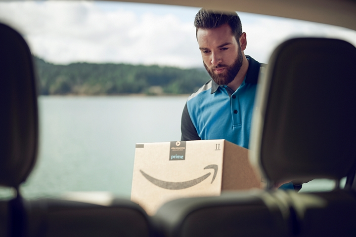 An amazon delivery man is placing an amazon box into the cargo area of a vehicle with a sunny scenic lake view in the background